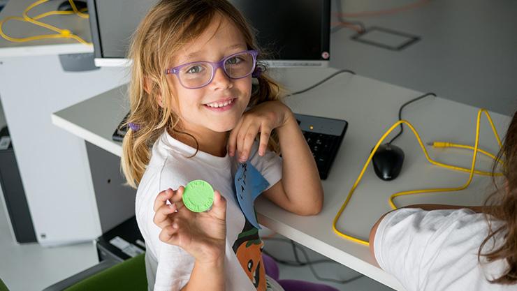 A little girl holding a green coin.