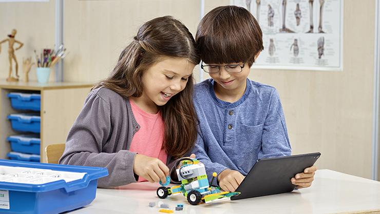 Children using a windows Laptop to program a Lego robot.